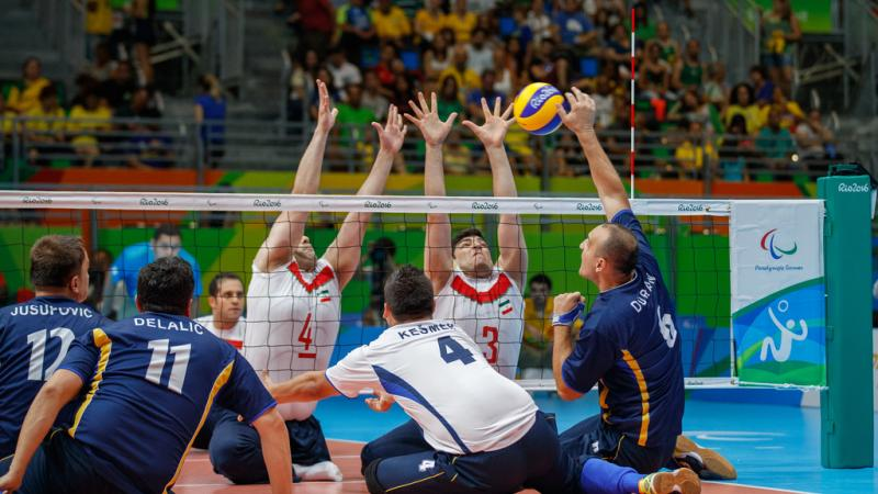 a group of male sitting volleyball players in action on the court
