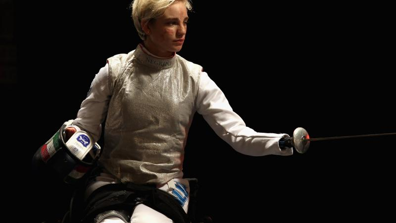 a female wheelchair fencer holds up her foil