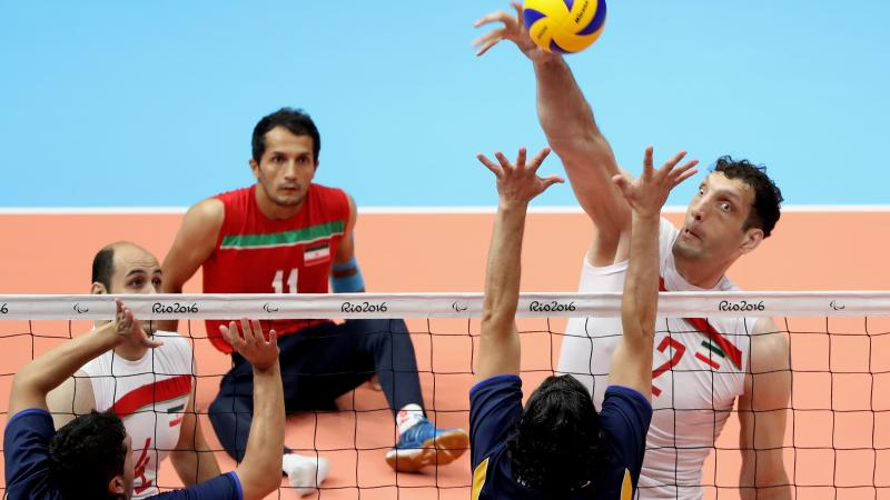a male sitting volleyball player attempts a block