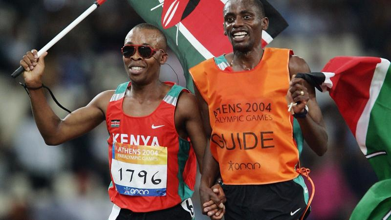 blind male runner Henry Wanyoike and his guide on a track carrying the Kenya flag