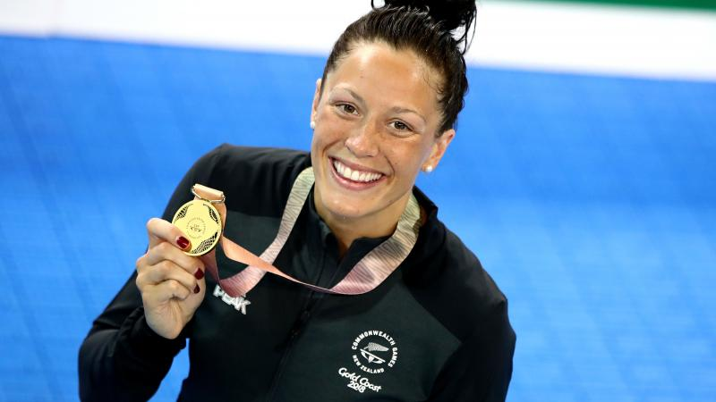 female Para swimmer Sophie Pascoe holds up a gold medal by the pool