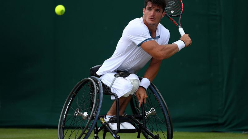 Argentinian male wheelchair tennis player hits a  a backhand shot