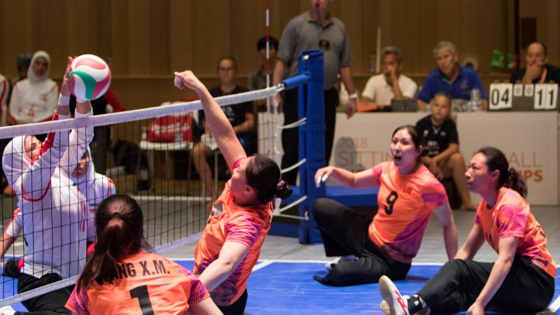 a female Chinese sitting volleyball player punches the ball over the net as her teammates watch