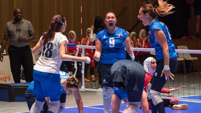 three female Italian sitting volleyball players celebrate on the court