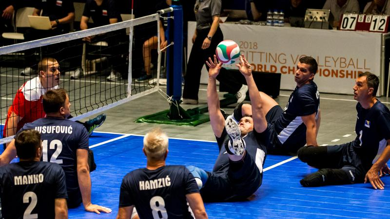 a group of Bosnian male sitting volleyball players working to get the ball back over the net