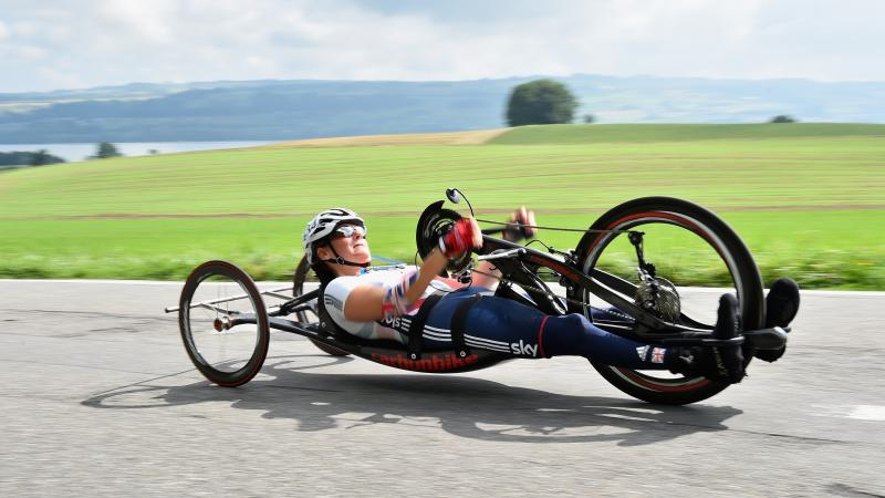 female British Para cyclist Karen Darke racing with a hand-bike on a road