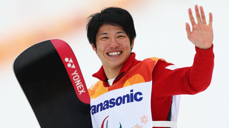male Para snowboarder Gurimu Narita holds his snowboard and waves to fans