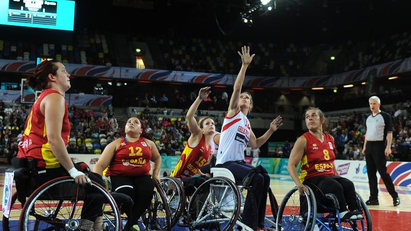 a group of female Spanish wheelchair basketballers fighting for the ball on the court