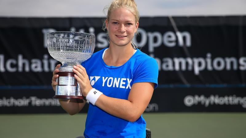 Female wheelchair tennis player Diede de Groot smiles and lifts a glass trophy