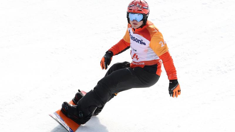Dutch male athlete rides snowboard down a slope