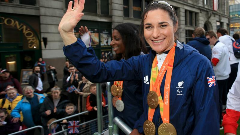 female Para cyclist Sarah Storey waves to fans from the top of a bus