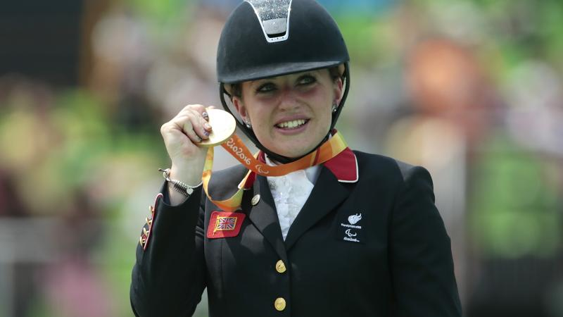 female Para equestrian rider Natasha Baker on the podium with her gold medal
