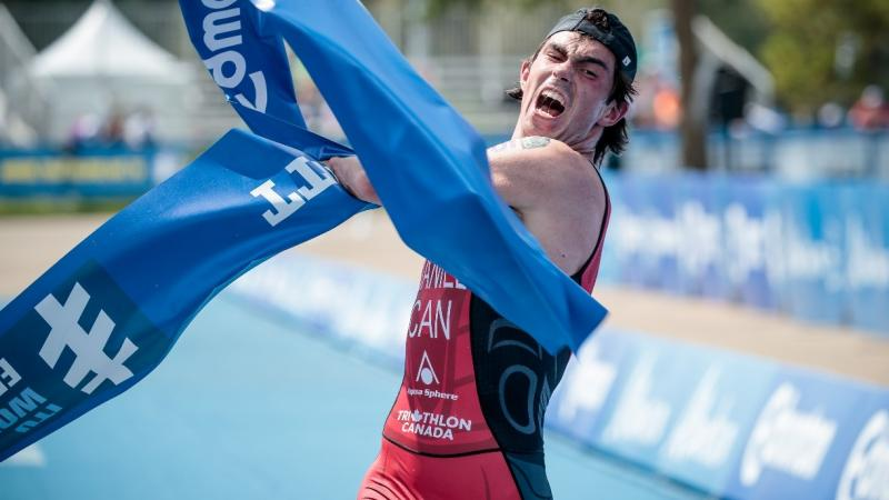 male Para triathlete Stefan Daniel rips the tape at the finishing line as he crosses to win the race
