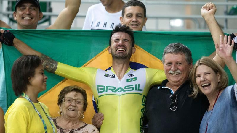 male Para cyclist Lauro Chaman celebrates with his family and holds up the Brazil flag
