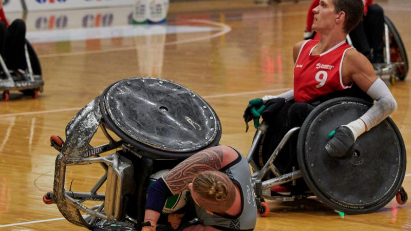 a Danish wheelchair rugby player on the ground after a tackle from a New Zealand wheelchair rugby player
