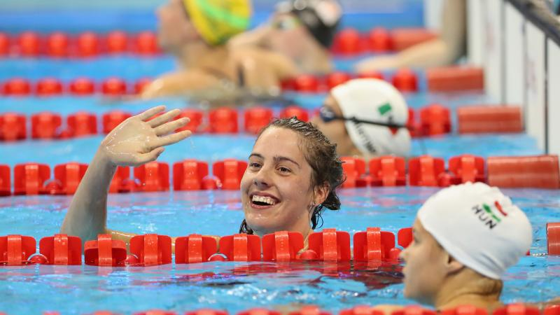 female Para swimmer Aurelie Rivard takes her swimming cap off and celebrates in the pool after winning a race