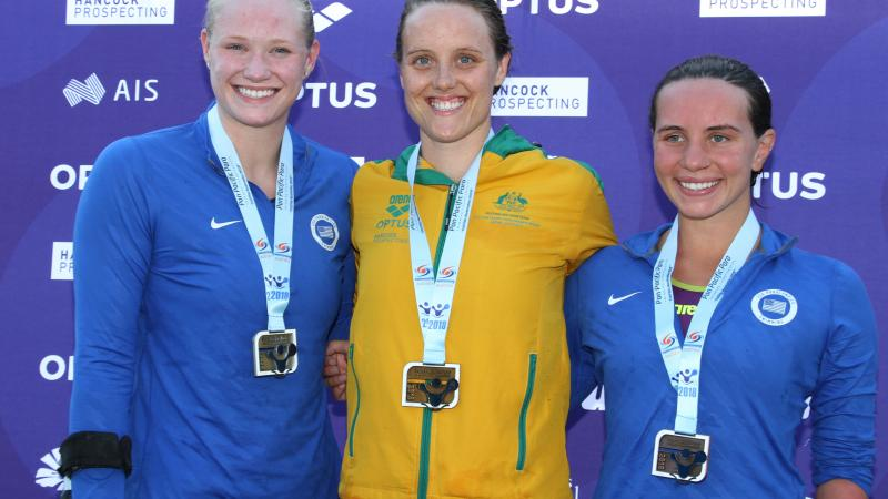 Three women with medals smiling