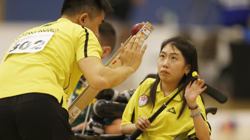female boccia player Ho Yuen Kei listens to her coach before taking a shot