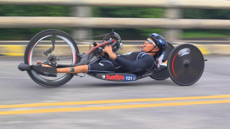 male Para triathlete Jumpei Kimura competing on a hand bike
