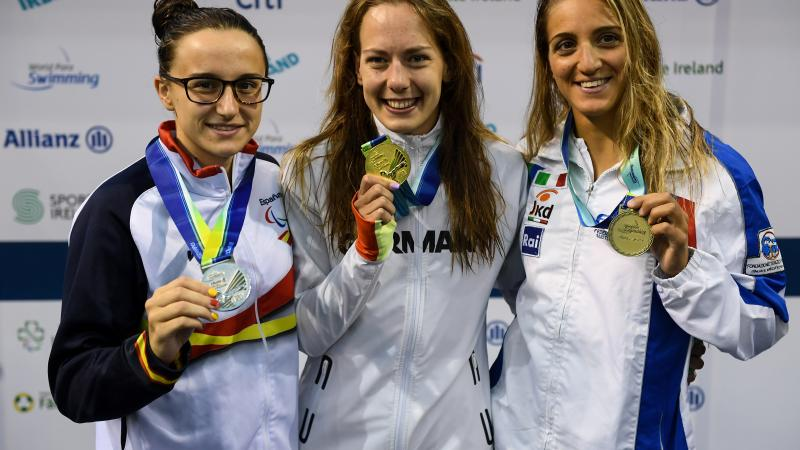 three female Para swimmers, with Naomi Maike Schnittger in the centre, holding up their medals