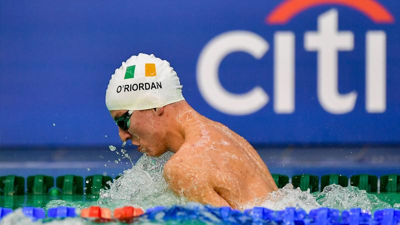 Athlete swimming with cap showing Ireland's flag