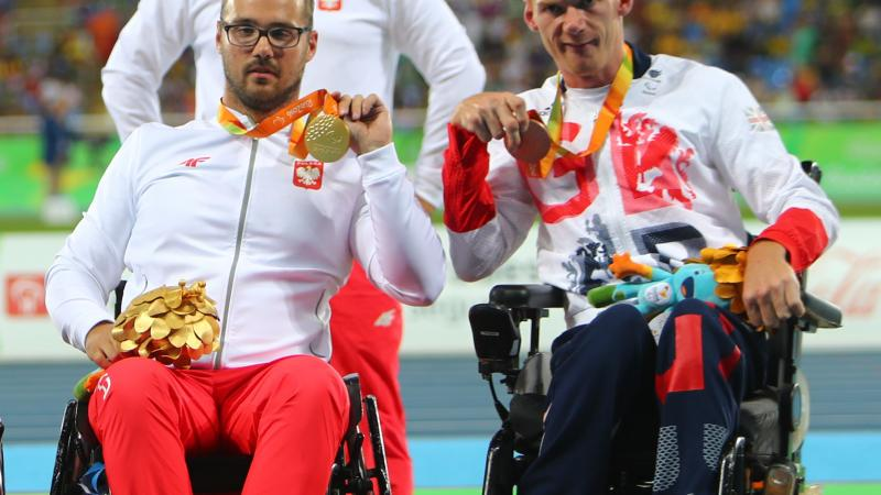 male Para athletes Stephen Miller and Maciej Sochal on the podium holding up their medals