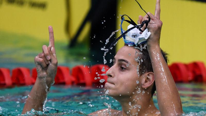 male Para swimmer Ugo Didier raises his fingers in celebration in the pool after winning his race