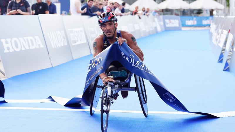 male Para triathlete Ahmed Andaloussi breaks the tape as he crosses the finish line