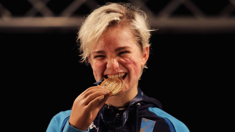 female wheelchair fencer Beatrice Vio bites a gold medal and smiles