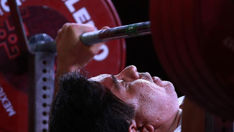 male powerlifter Majid Farzin prepares to lift the bar
