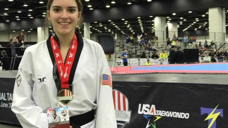 US woman taekwondo fighter poses with medal around her neck