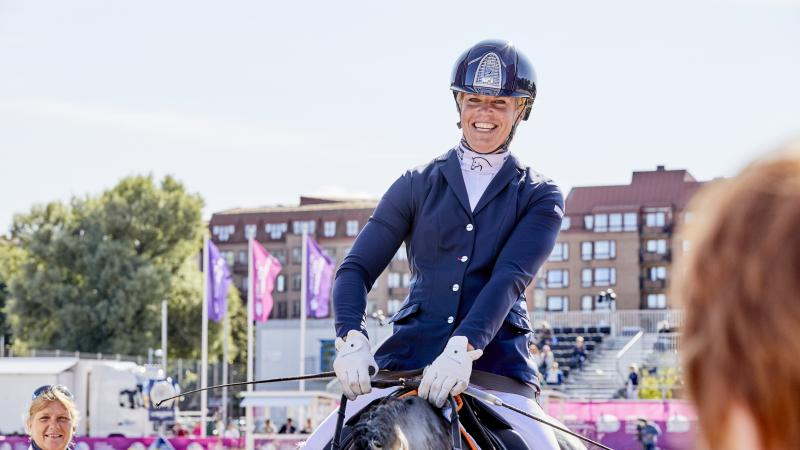 Dutch female rider smiles on her horse