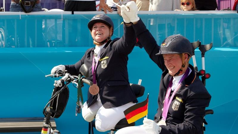 female Para equestrian rider Angelika Trabert celebrates with the German flag and her medal