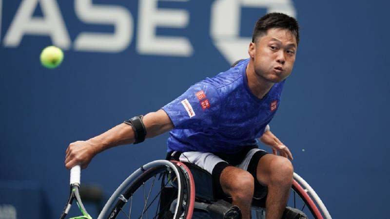 Japanese man in wheelchair reaches to his tennis ball