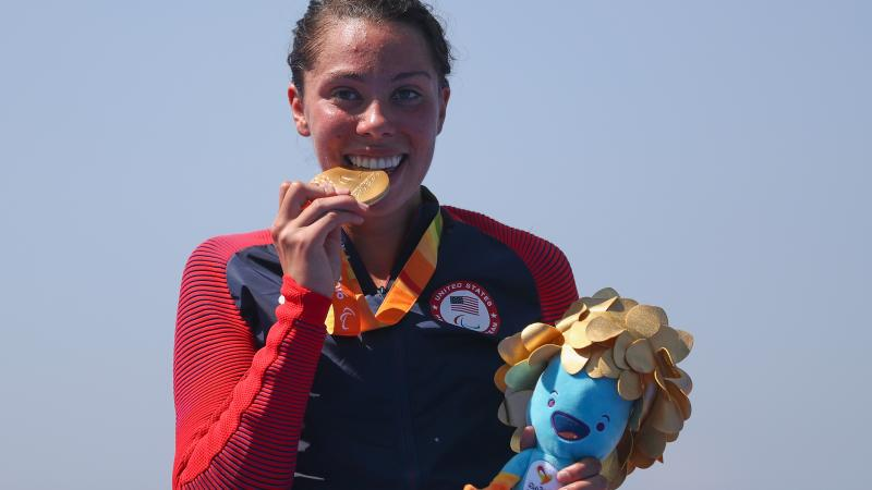 female Para triathlete Grace Norman bites her gold medal on the podium