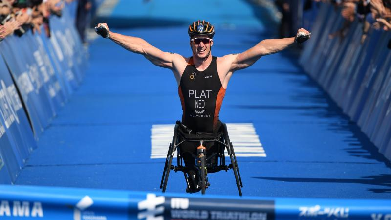 male Para triathlete raises his arms in celebration as he breaks the finish line tape
