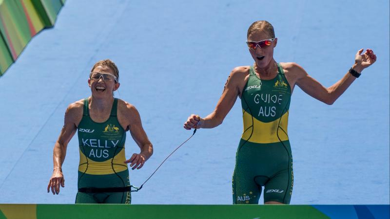 female Para triathlete Katie Kelly and female guide Michellie Jones break the finish tape