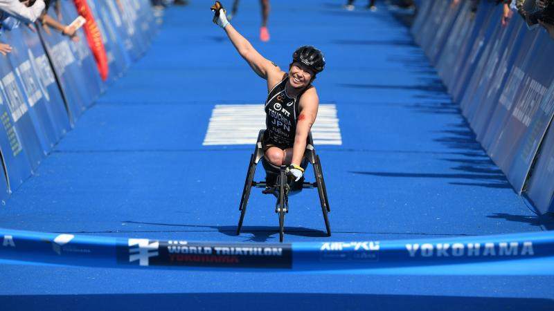 Japanese female Para triathlete Wakako Tsuchida punches the air as she crosses the finish line