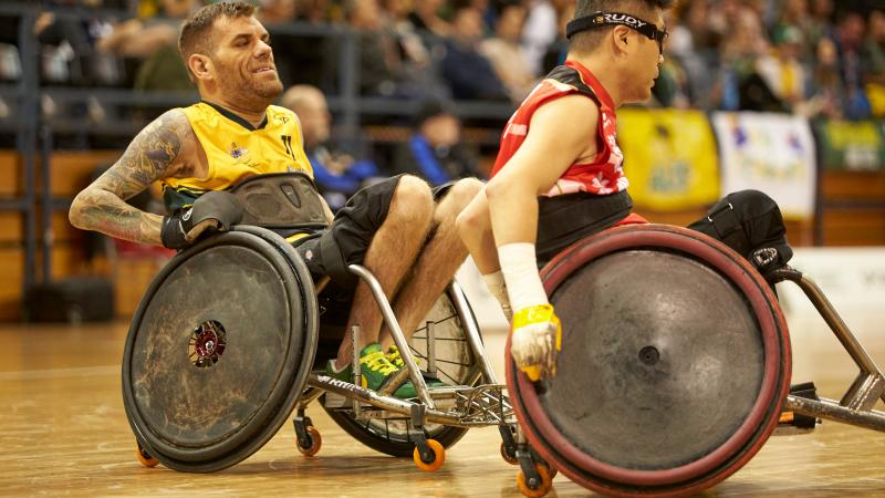 male wheelchair rugby player Ryan Scott chases another player with the ball