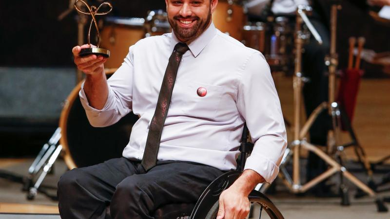 male wheelchair fencer Jovane Guissone holds up a trophy