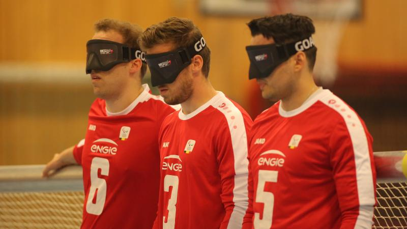 three Belgian male goalball players lined up in a row