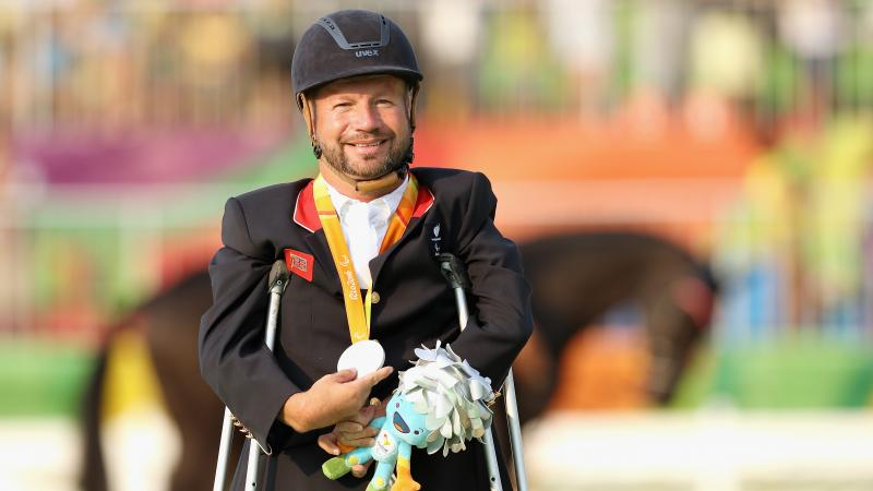 male Para equestrian rider Lee Pearson standing on crutches holding a medal