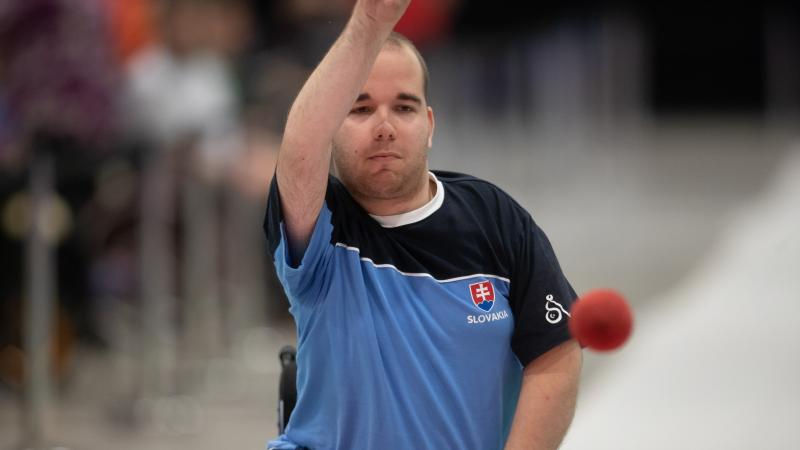 Male boccia player throws red ball