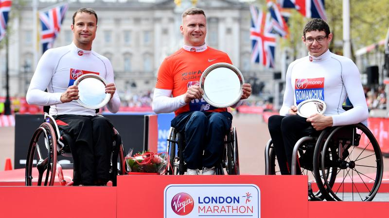 three male wheelchair racers including Marcel Hug and David Weir on a podium holding trophies