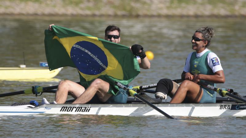 A man and woman in rowing boat celebrate, while man holds up Brazilian flag