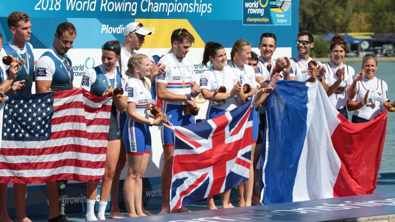 Group of female and male rowers on the podium with USA, Great Britain and France flags