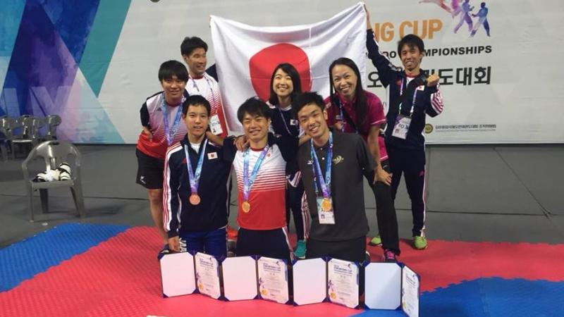 a group of Japanese Para taekwondo fighters with their medals and a Japan flag