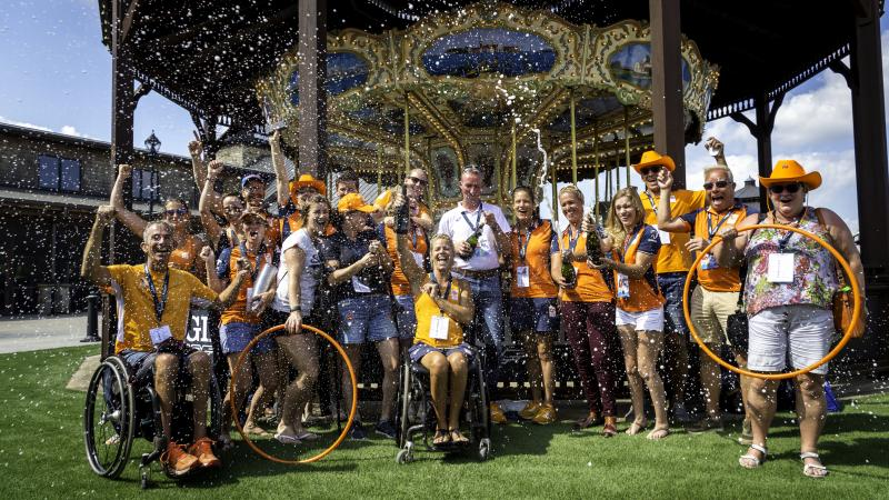 Group photo of Dutch Para equestrian team dressed in orange team colors celebrating with champagne