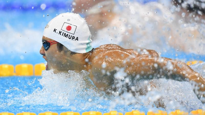 Man swimming with a cap showing the Japanese flag