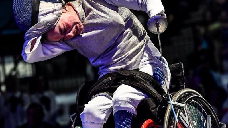 Italian female wheelchair fencer takes off her mask after a win